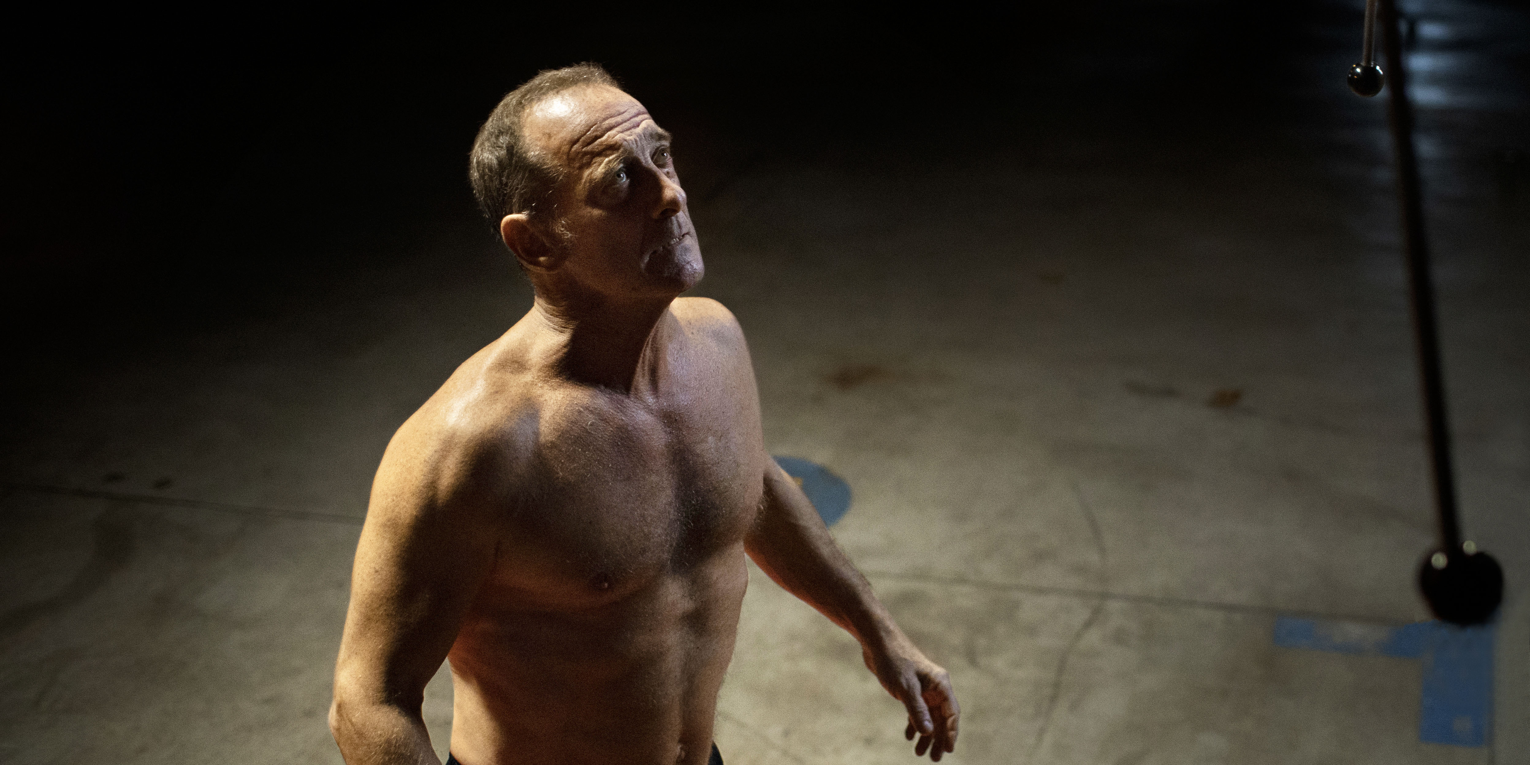 A bare chested man standing in an empty space looks up