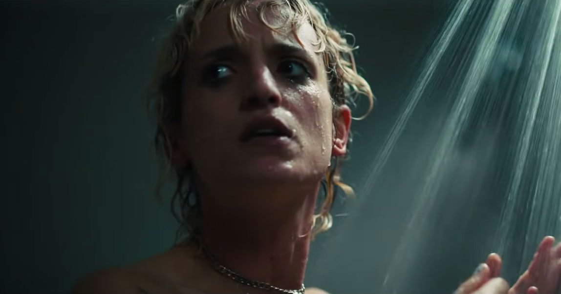 A blonde woman stands in the shower (visible from the neck up)