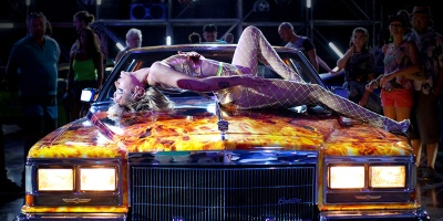 A woman reclines on the hood of a car